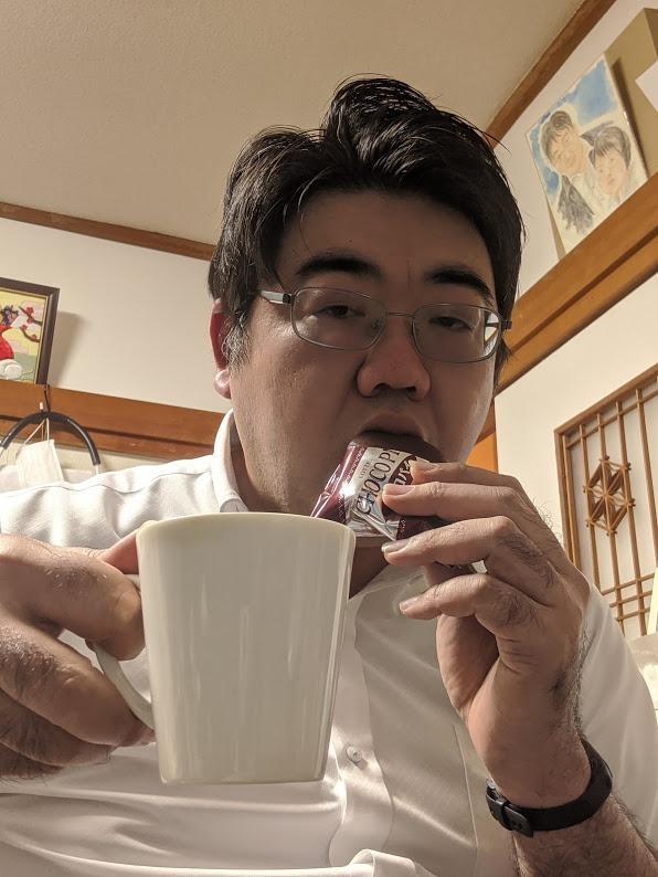 コーヒーを片手にチョコ菓子を頬張るくらげの写真