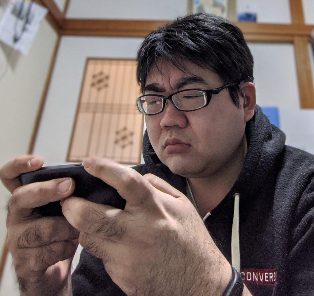 PUBGをプレイ中のくらげを写した写真。スマートフォンを握りしめて眉をしかめている