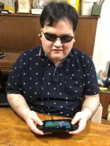 PS4を手にイヤホンから流れる音に注力しながらパワフルプロ野球をプレイする著者・北村直也の写真