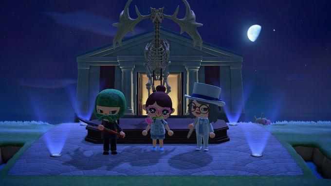 月が輝く中、恐竜の化石と神殿を背景にした、あつ森「ケイドロ遊び」泥棒チーム3人の記念写真。