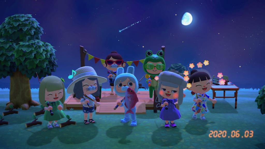 あつ森「釣り大会」の記念撮影。日も暮れ、月が照らし流れ星輝く中、7人のプレイヤーが笑顔で写っている。2020年6月3日