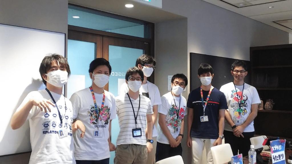富士通eSports部のメンバー7人の写真。全員がマスクをつけ、社員証を首にさげている。