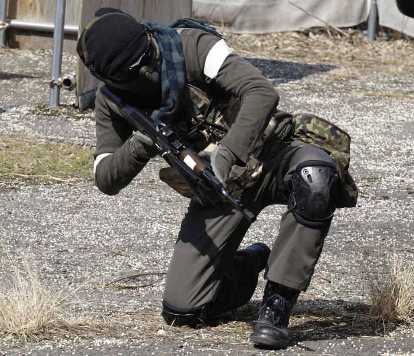サバイバルゲーム中の様子。銃を斜め下に構えながら片膝をつき、敵へと照準を合わせている。