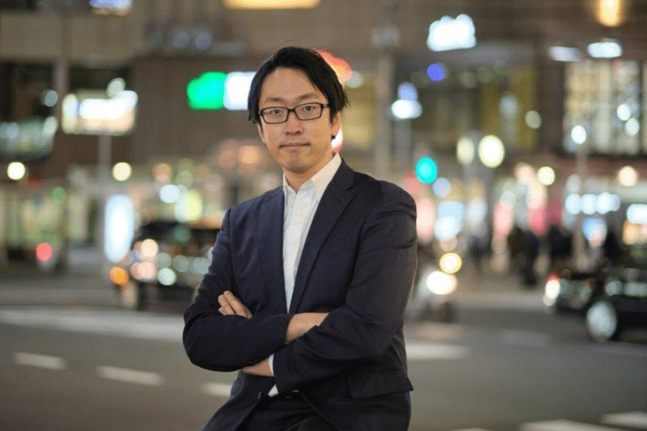 ePARA(イーパラ)代表・加藤大貴の写真。夜の交差点を背景に腕組みをして前を見つめている。