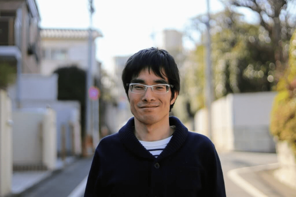 筆者・ジョジョの写真。閑静な住宅街を背景に、白い眼鏡をかけたジョジョが優しい微笑みを浮かべている。