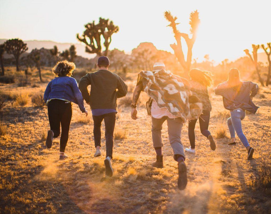 夕日に向かって走る若者たちのイメージ写真。